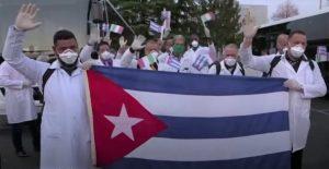 Ärzte aus Kuba helfen in Italien gegen das Corona Virus anzukämpfen. Das Bild zeigt kubanische Ärzte, die eine Fahne ihres Landes halten.