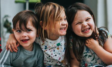 Staatsbürgerschaft Österreich: drei Kinder sitzen auf Stufe und umarmen sich